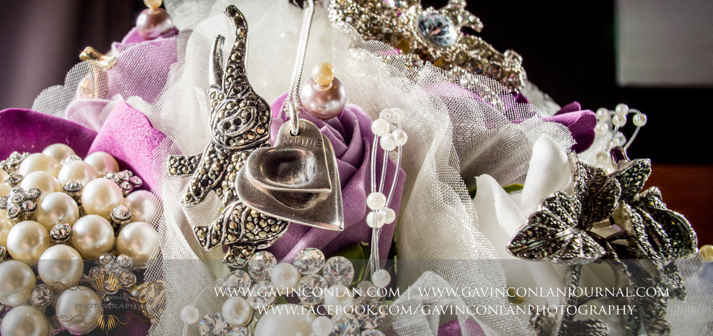 bouquet showcasing brooches multiple family heirlooms - a touching tribute. Wedding photography at  The Essex Golf and Country Club  by  gavin conlan photography Ltd