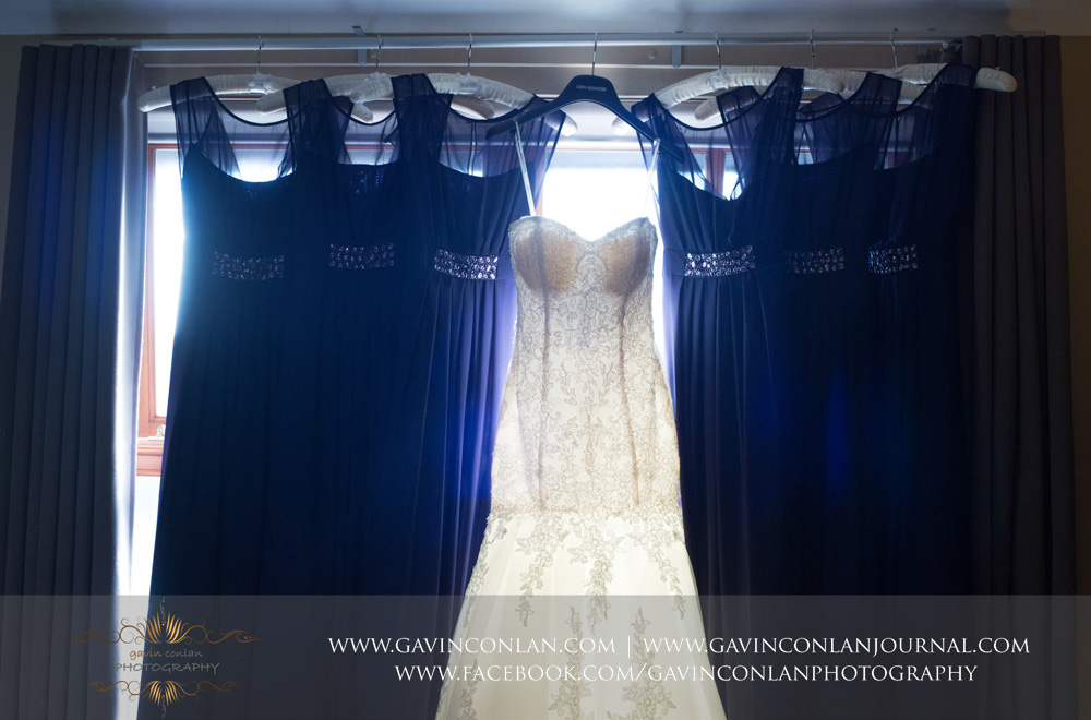 bride and bridesmaids dresses hanging in the window. Wedding photography at  The Essex Golf and Country Club  by  gavin conlan photography Ltd