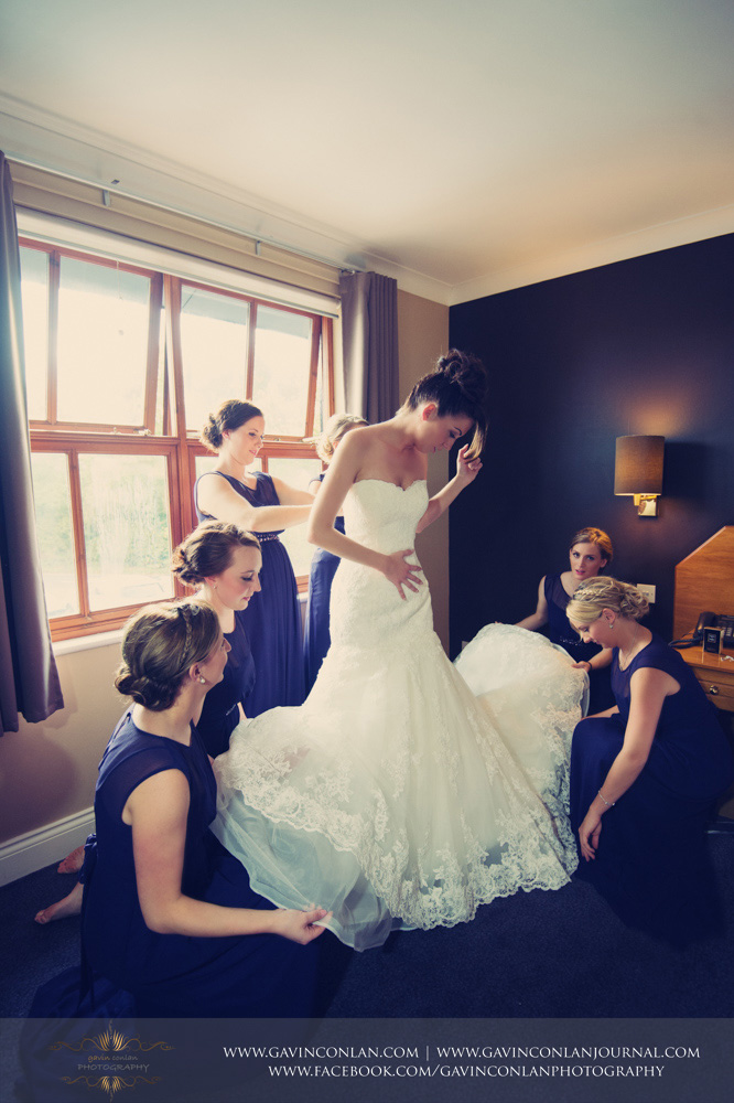 creative portrait of the bridesmaids helping the bride to get dressed. Wedding photography at  The Essex Golf and Country Club  by  gavin conlan photography Ltd