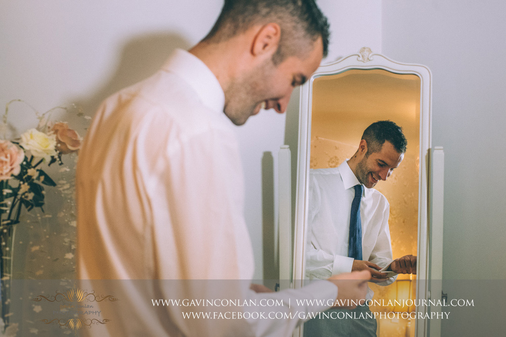 the groom laughing whilst putting on his cuff links. Wedding photography at  Crabbs Barn  by  gavin conlan photography Ltd