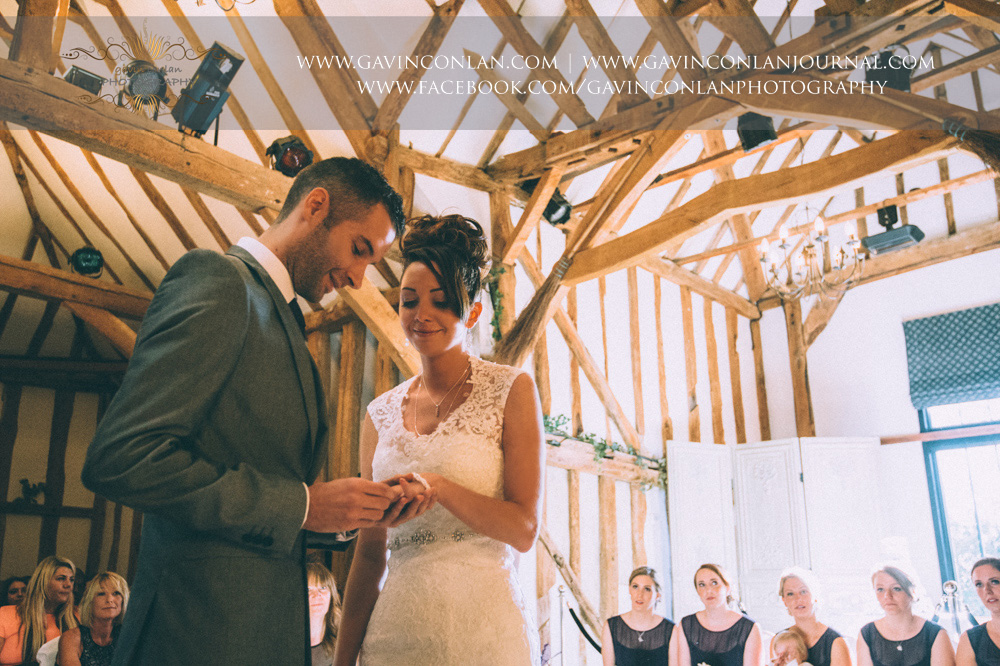 groom putting the ring on his brides finger during the wedding ceremony. Wedding photography at  Crabbs Barn  by  gavin conlan photography Ltd