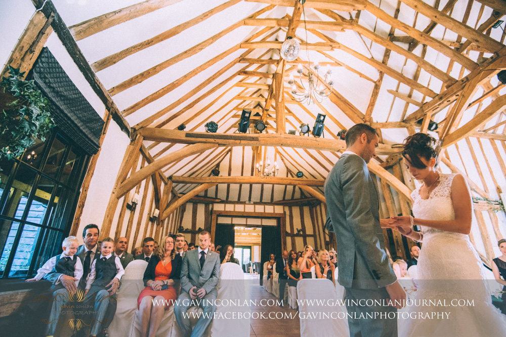 bride putting ring on her grooms finger during the wedding ceremony. Wedding photography at  Crabbs Barn  by  gavin conlan photography Ltd