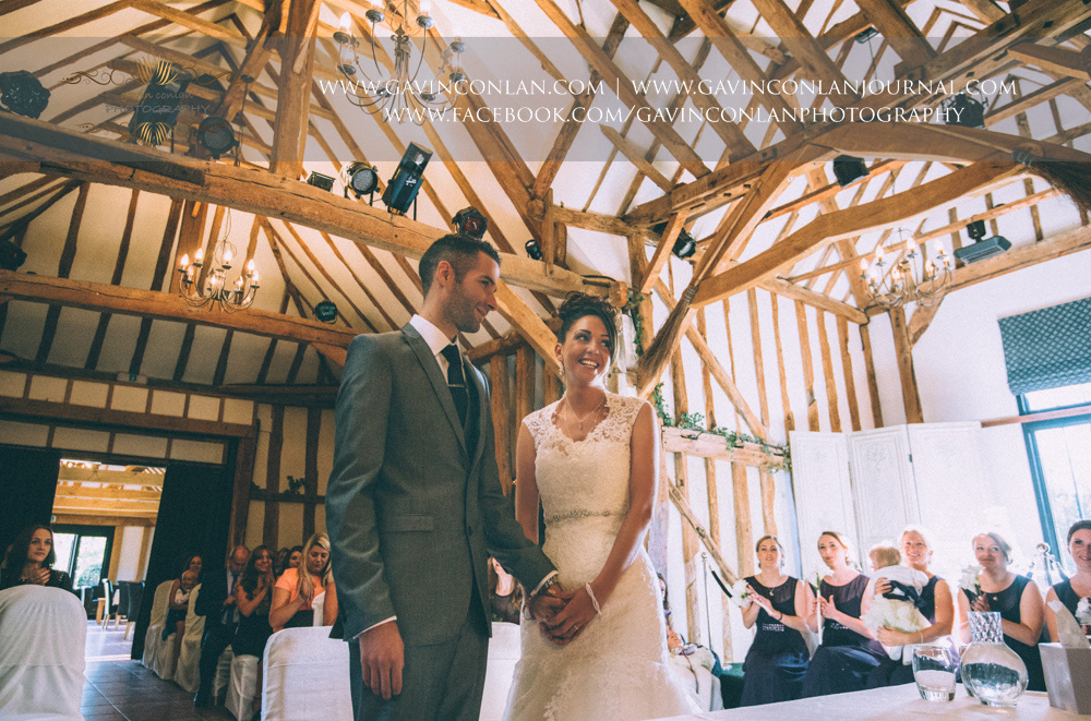 bride and groom complete the exchanging of their rings during their wedding ceremony. Wedding photography at  Crabbs Barn  by  gavin conlan photography Ltd
