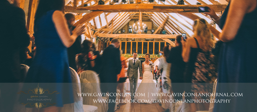 bride and groom walking down the aisle as a married couple. Wedding photography at  Crabbs Barn  by  gavin conlan photography Ltd