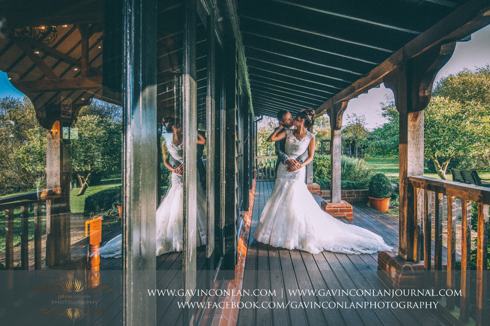 creative portrait with the use of reflections of the bride and groom kissing on the balcony at Crabbs Barn. Wedding photography at  Crabbs Barn  by  gavin conlan photography Ltd