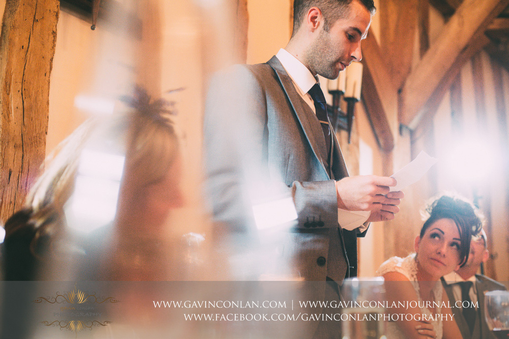 creative portrait of the groom during his speech with his bride looking up at him. Wedding photography at  Crabbs Barn  by  gavin conlan photography Ltd