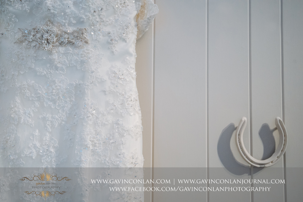 a creative close up detail shot of the brides stunning dress at  Coworth Park Hotel  by  gavin conlan photography Ltd