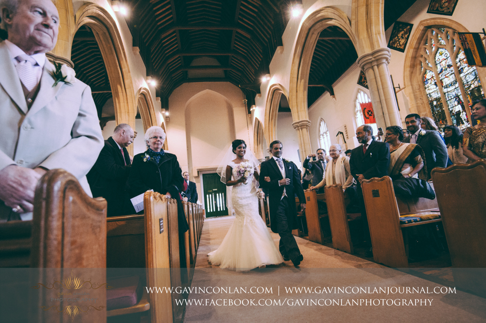 the bride walking down the aisle with her father at  All Saints Church in Marlow  by  gavin conlan photography Ltd