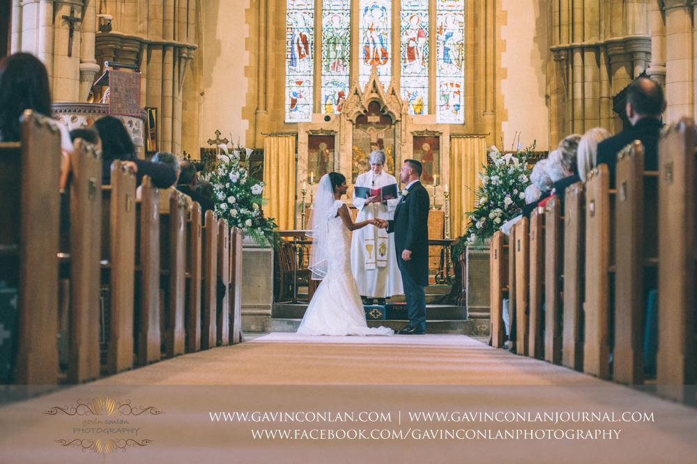 bride and groom holding hands and saying their wedding vows, wedding photography at  All Saints Church Marlow  by  gavin conlan photography Ltd