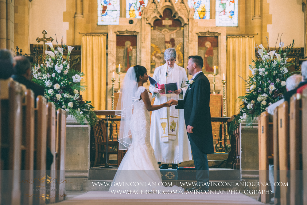 bride and groom holding hands during the ceremony, wedding photography at  All Saints Church Marlow  by  gavin conlan photography Ltd