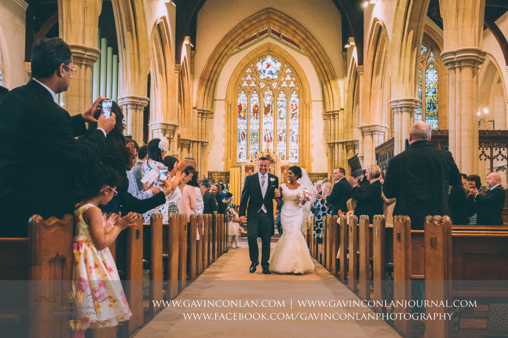 bride and groom walking down the aisle as husband and wife, wedding photography at  All Saints Church Marlow  by  gavin conlan photography Ltd