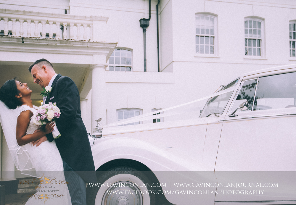 creative bride and groom portrait with their wedding car, wedding photography at  Heatherden Hall Pinewood Studios  by  gavin conlan photography Ltd