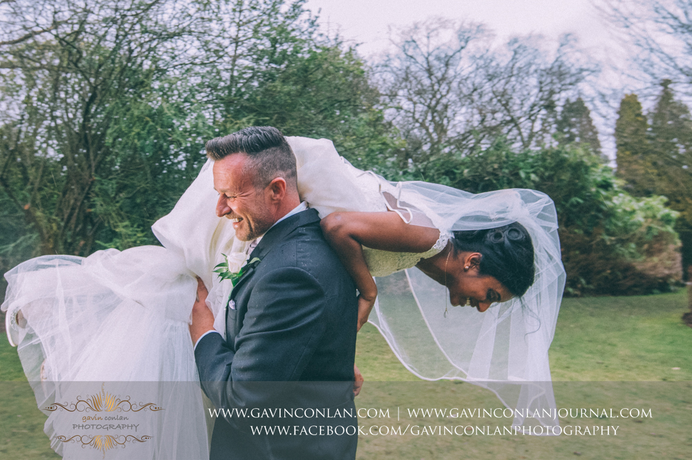 the groom carrying his bride over his shoulder, wedding photography at  Heatherden Hall Pinewood Studios  by  gavin conlan photography Ltd