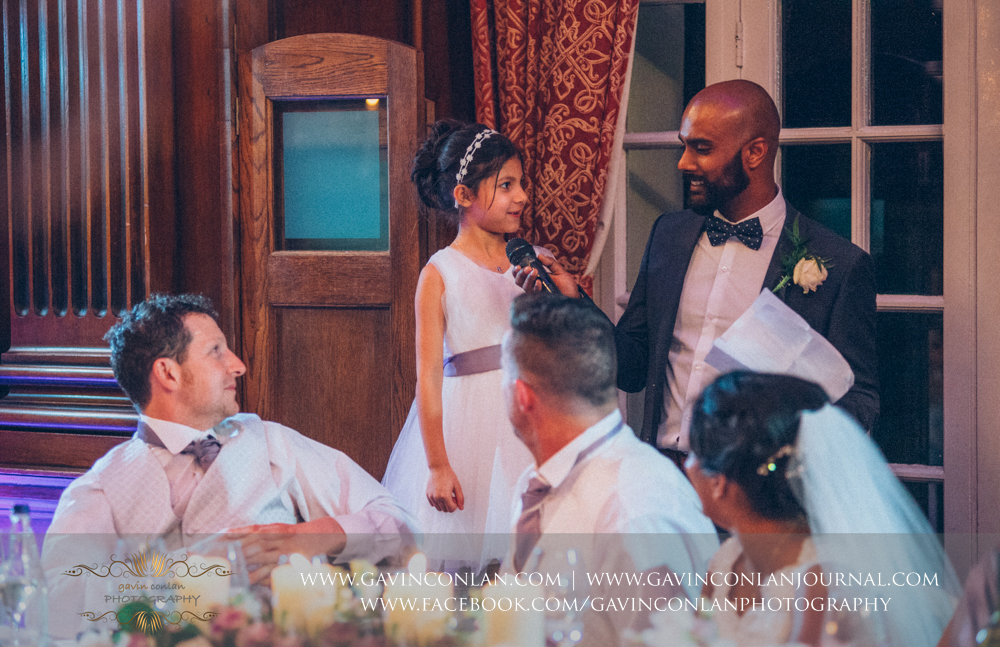 the flower girl helping the brother of the bride doing his speech, wedding photography at  Heatherden Hall Pinewood Studios  by  gavin conlan photography Ltd