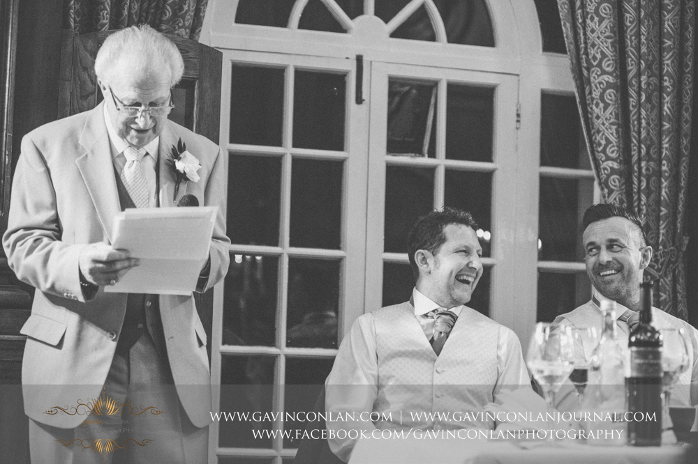 the father of the groom giving his speech with the groom and best man laughing, wedding photography at  Heatherden Hall Pinewood Studios  by  gavin conlan photography Ltd