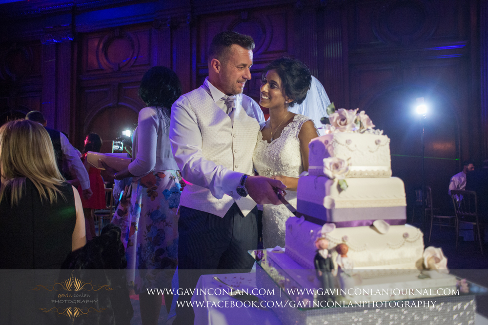 the bride and groom cutting their wedding cake, wedding photography at  Heatherden Hall Pinewood Studios  by  gavin conlan photography Ltd
