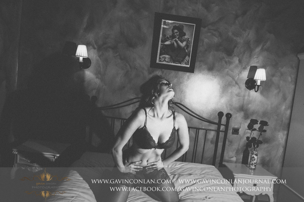 black and white photograph of a beautiful woman in sexy red underwear posing on the bed. London boudoir photography by gavin conlan photography Ltd
