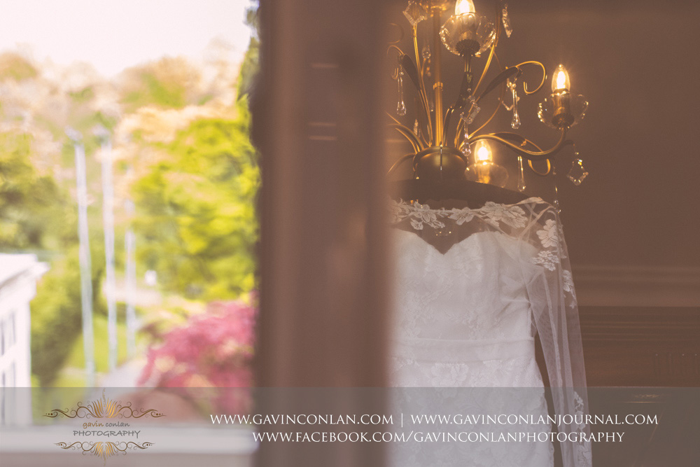 creative reflective detail shot of the bride's beautiful wedding dress hanging in front of the four poster bed. Wedding photography at The SPA Hotel by  gavin conlan photography Ltd