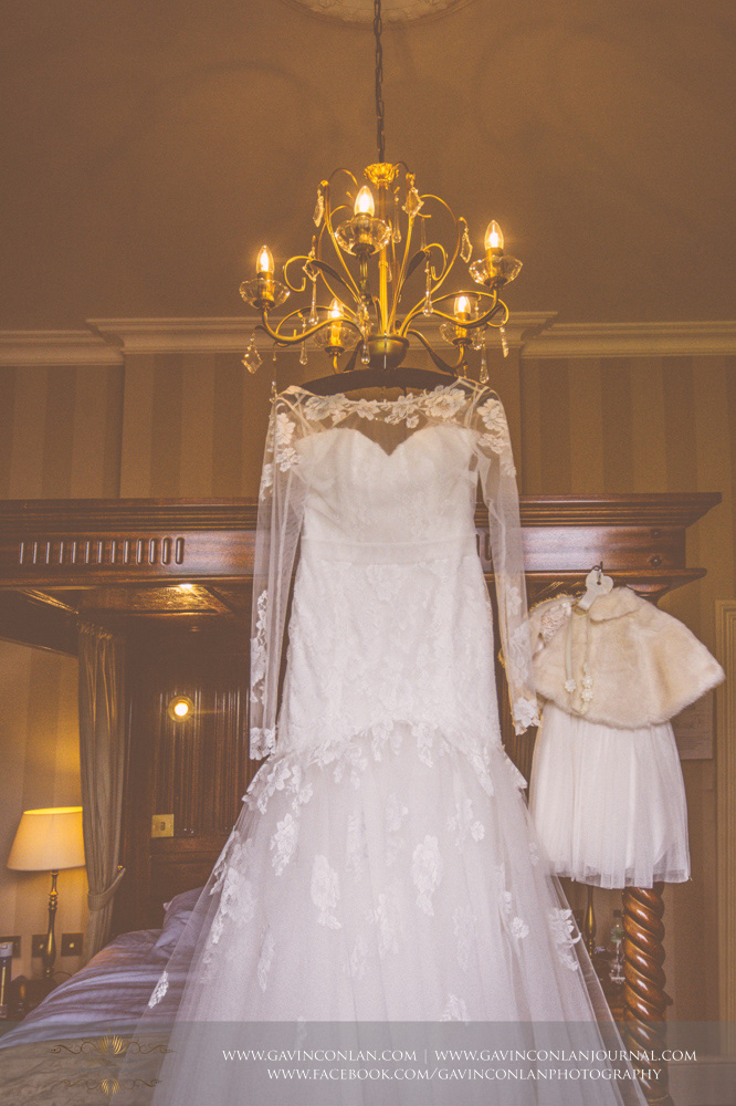 creative detail shot of the bride's beautiful wedding dress hanging in front of the four poster bed next to her baby daughters dress. Wedding photography at  The SPA Hotel  by  gavin conlan photography Ltd