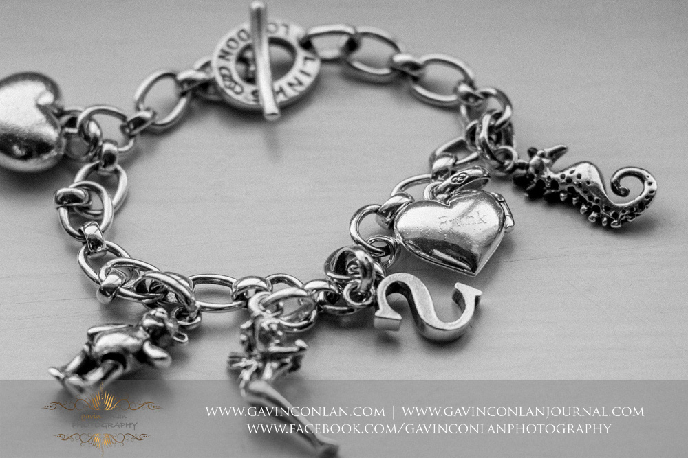 close up of the brides bracelet containing sentimental details. Wedding photography at  The SPA Hotel  by  gavin conlan photography Ltd