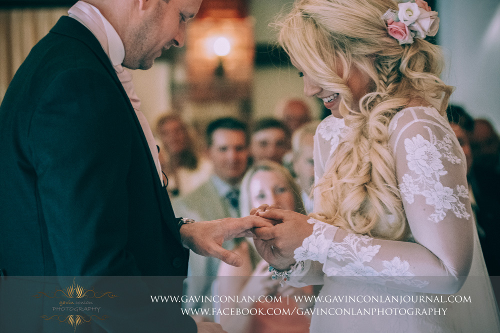 the bride placing the wedding ring on her grooms finger. Wedding photography at  High Rocks  by preferred supplier  gavin conlan photography Ltd