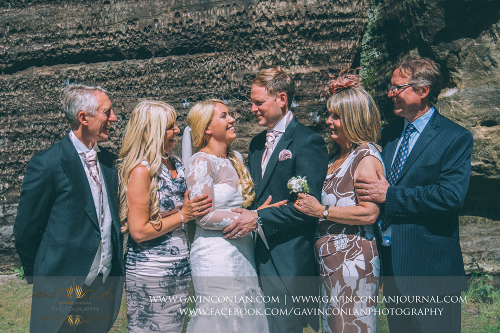 creative portrait of the bride and groom with both sets of parents in the grounds of The Rocks. Wedding photography at  High Rocks  by preferred supplier  gavin conlan photography Ltd
