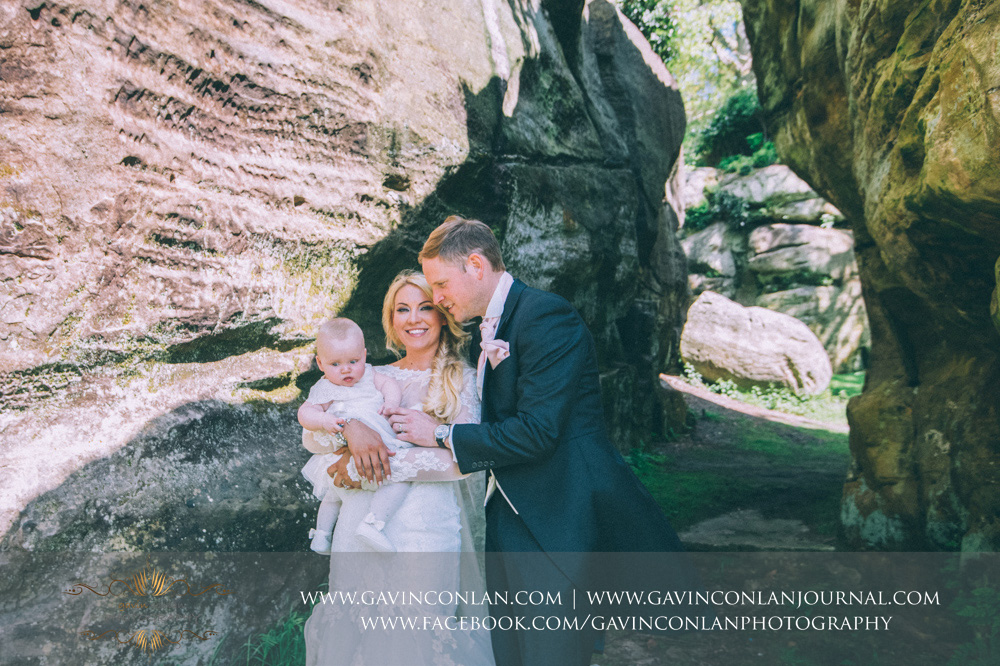 creative portrait of the bride and groom with their beautiful daughter in the grounds of The Rocks. Wedding photography at  High Rocks  by preferred supplier  gavin conlan photography Ltd
