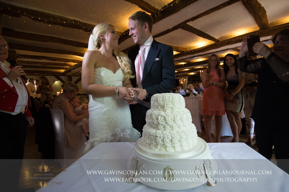 creative portrait of the bride and groom just before they cut their wedding cake whilst smiling at each other. Wedding photography at  High Rocks  by preferred supplier  gavin conlan photography Ltd