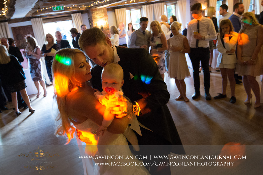 the bride and groom with their daughter during their first dance. Wedding photography at  High Rocks  by preferred supplier  gavin conlan photography Ltd