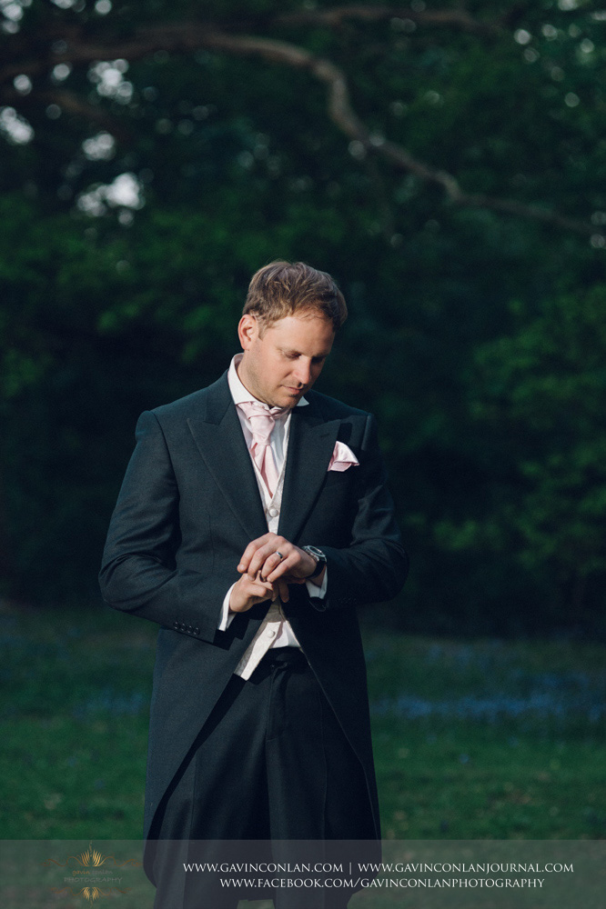 a portrait of the groom posing whilst looking at his watch standing in front of bluebells. Wedding photography at  High Rocks  by preferred supplier  gavin conlan photography Ltd