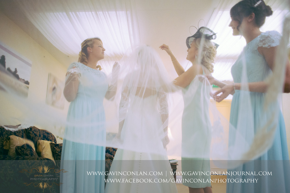 creative portrait of the bridesmaids helping the bride getting ready in the bridal suite. Wedding photography at Parklands Quendon Hall by preferred supplier gavin conlan photography Ltd