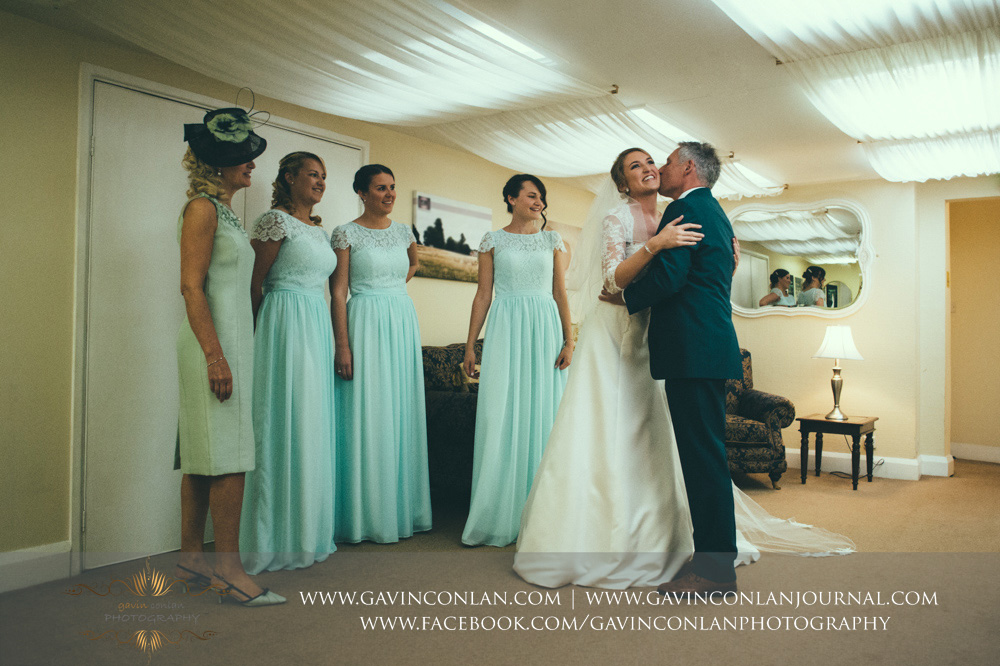 a beautiful portrait of the brides father seeing her daughter in her wedding dress for the first time, he gives his daughter a kiss on the cheek whilst her mother and bridesmaids look on with joy. Wedding photography at  Parklands Quendon Hall  by preferred supplier  gavin conlan photography Ltd