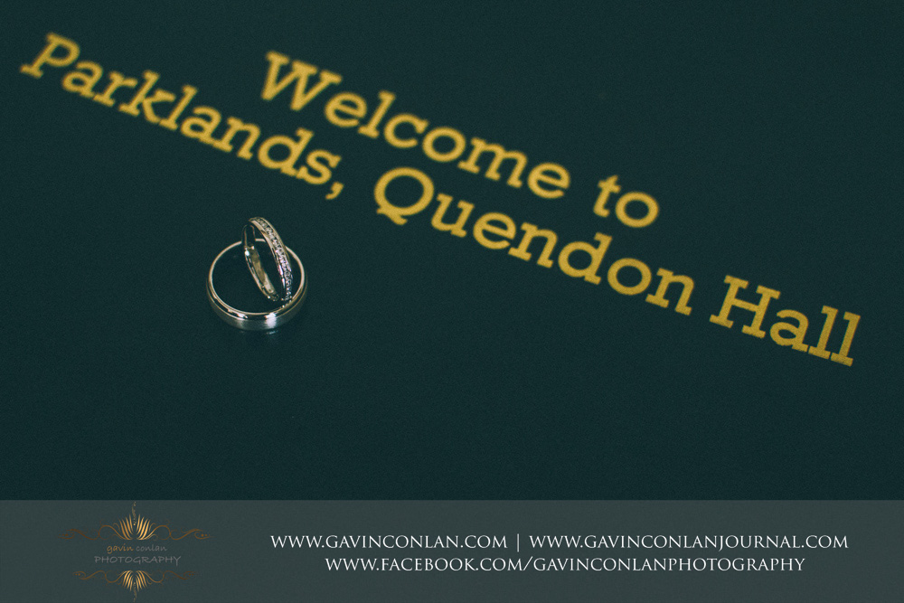 creative detail photograph of the bride and grooms wedding rings with welcome to Parklands, Quendon Hall in the background. Wedding photography at  Parklands Quendon Hall  by preferred supplier  gavin conlan photography Ltd