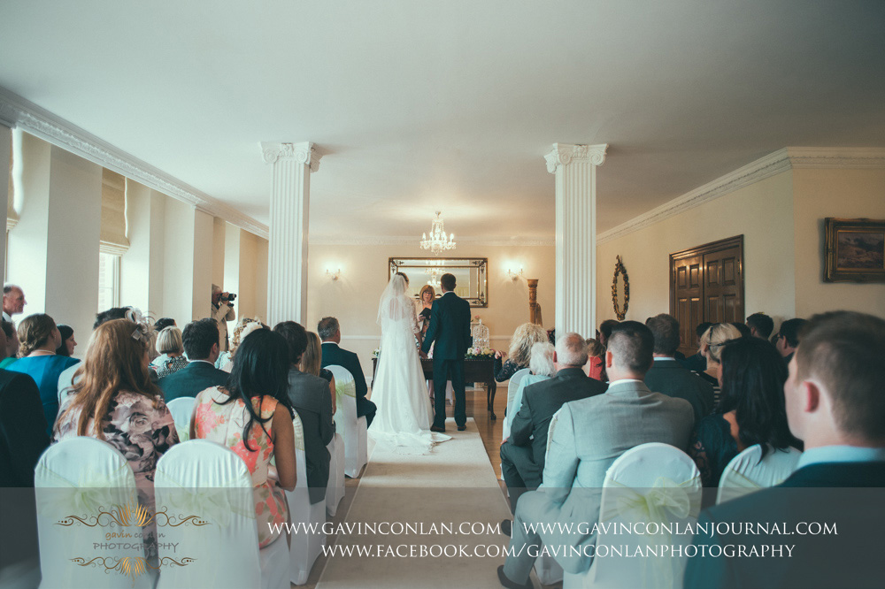 creative portrait of the bride and groom holding hands during the wedding ceremony. Wedding photography at Parklands Quendon Hall by preferred supplier gavin conlan photography Ltd