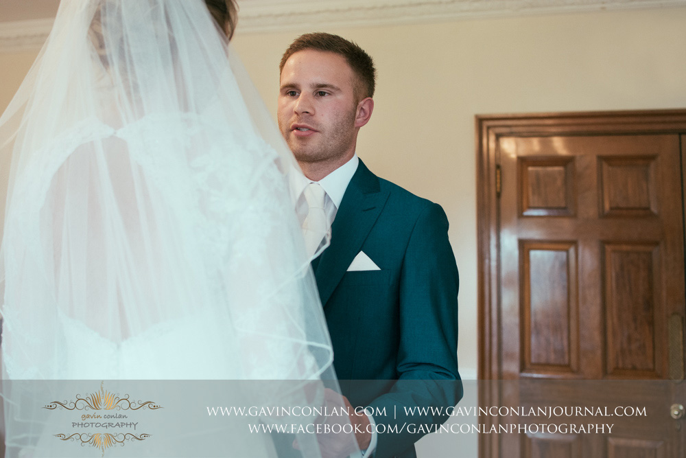 creative portrait of the groom looking at his bride saying his vows during the wedding ceremony. Wedding photography at Parklands Quendon Hall by preferred supplier gavin conlan photography Ltd