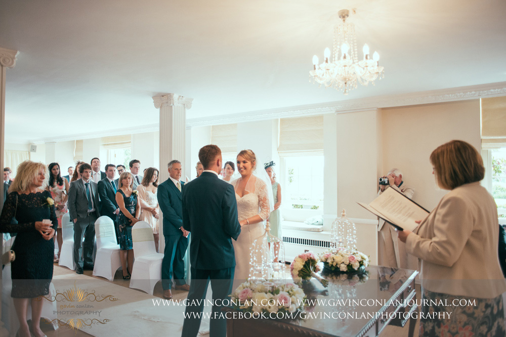 creative portrait of the bride and groom looking at each other holding hands as they say their vows during the wedding ceremony. Wedding photography at  Parklands Quendon Hall  by preferred supplier  gavin conlan photography Ltd