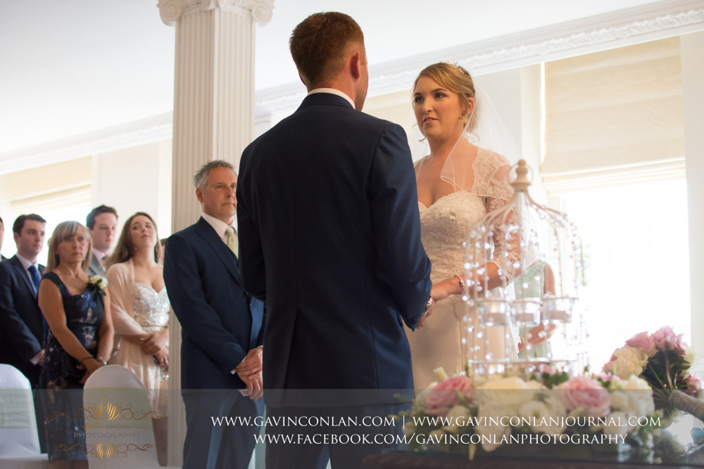 creative portrait of the bride looking at her groom saying her vows during the wedding ceremony. Wedding photography at  Parklands Quendon Hall  by preferred supplier  gavin conlan photography Ltd