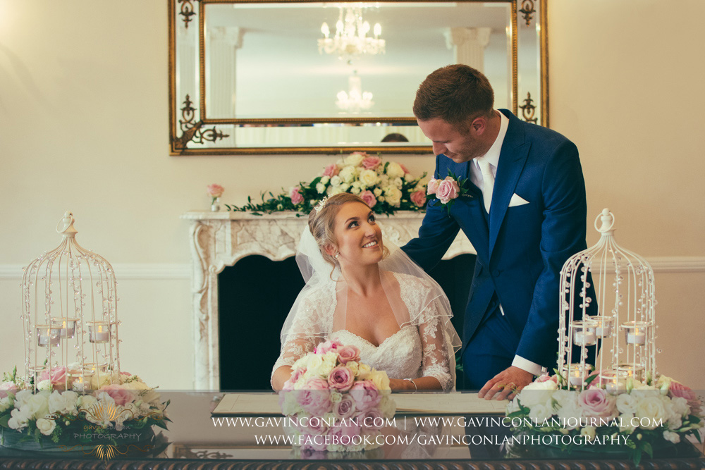 creative portrait of the bride and groom looking at each other during the signing of the register - a beautiful moment at the end of their wedding ceremony. Wedding photography at  Parklands Quendon Hall  by preferred supplier  gavin conlan photography Ltd