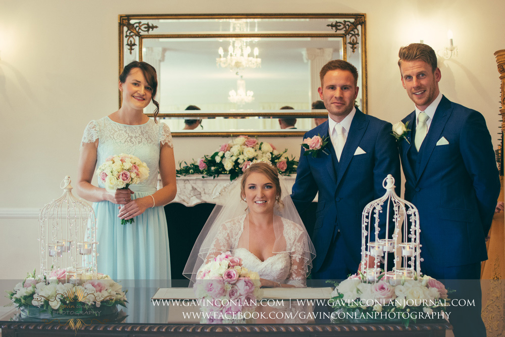 creative portrait of the bride, groom and their two witnesses - a beautiful moment at the end of their wedding ceremony. Wedding photography at Parklands Quendon Hall by preferred supplier gavin conlan photography Ltd