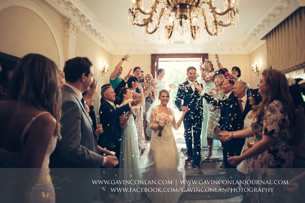 creative portrait of the guests throwing confetti over the bride and groom as they enter Parklands. Wedding photography at  Parklands Quendon Hall  by preferred supplier  gavin conlan photography Ltd