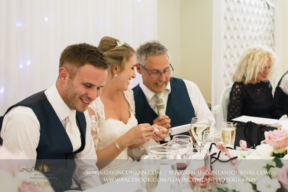 father of the bride crouched down next to his daughter during his speech. Wedding photography at  Parklands Quendon Hall  by preferred supplier  gavin conlan photography Ltd
