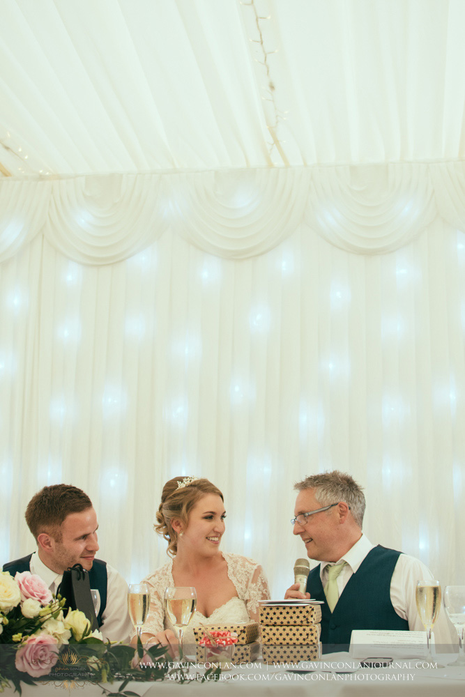 father of the bride crouched down next to his daughter as the groom looks on with a smile. Wedding photography at  Parklands Quendon Hall  by preferred supplier  gavin conlan photography Ltd