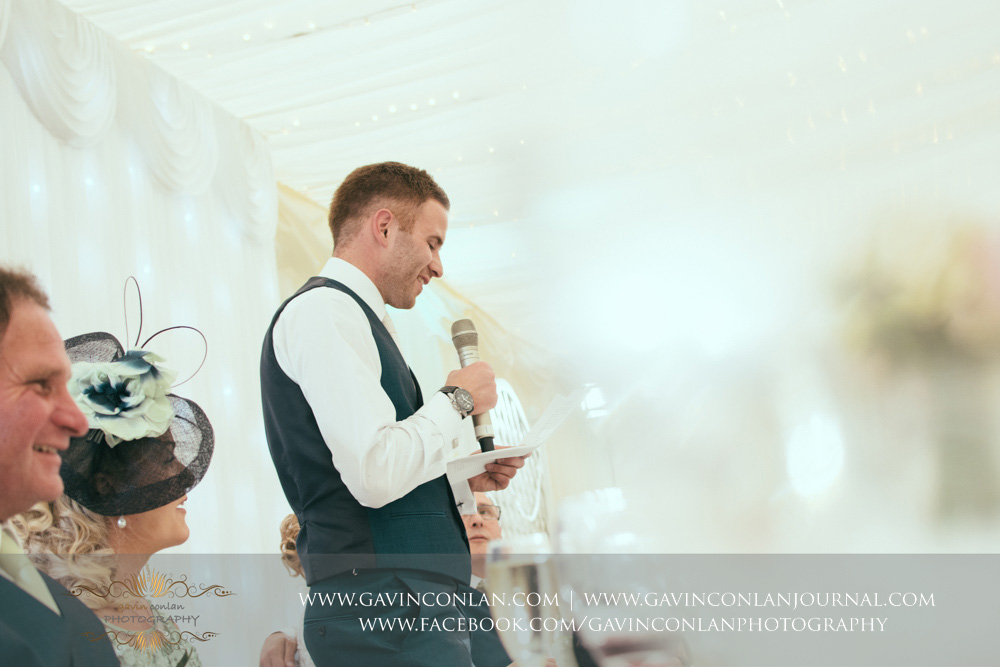 creative portrait of the groom during his speech with his father smiling in the foreground. Wedding photography at  Parklands Quendon Hall  by preferred supplier  gavin conlan photography Ltd