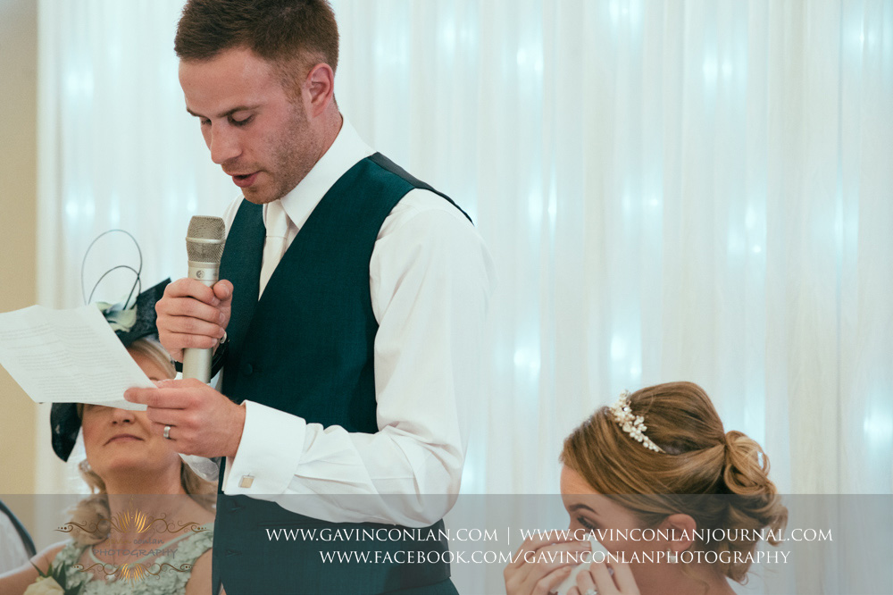 creative portrait of the groom during his speech with his bride wiping away a tear from her eye. Wedding photography at  Parklands Quendon Hall  by preferred supplier  gavin conlan photography Ltd
