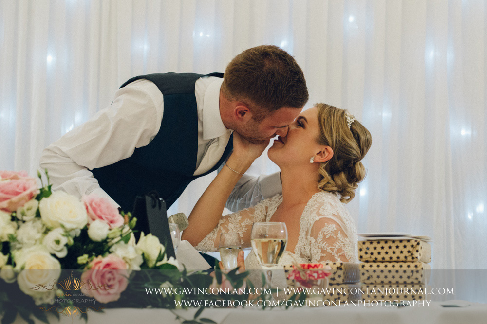 creative portrait of the bride and groom sharing a kiss after the groom finishes his speech. Wedding photography at Parklands Quendon Hall by preferred supplier gavin conlan photography Ltd