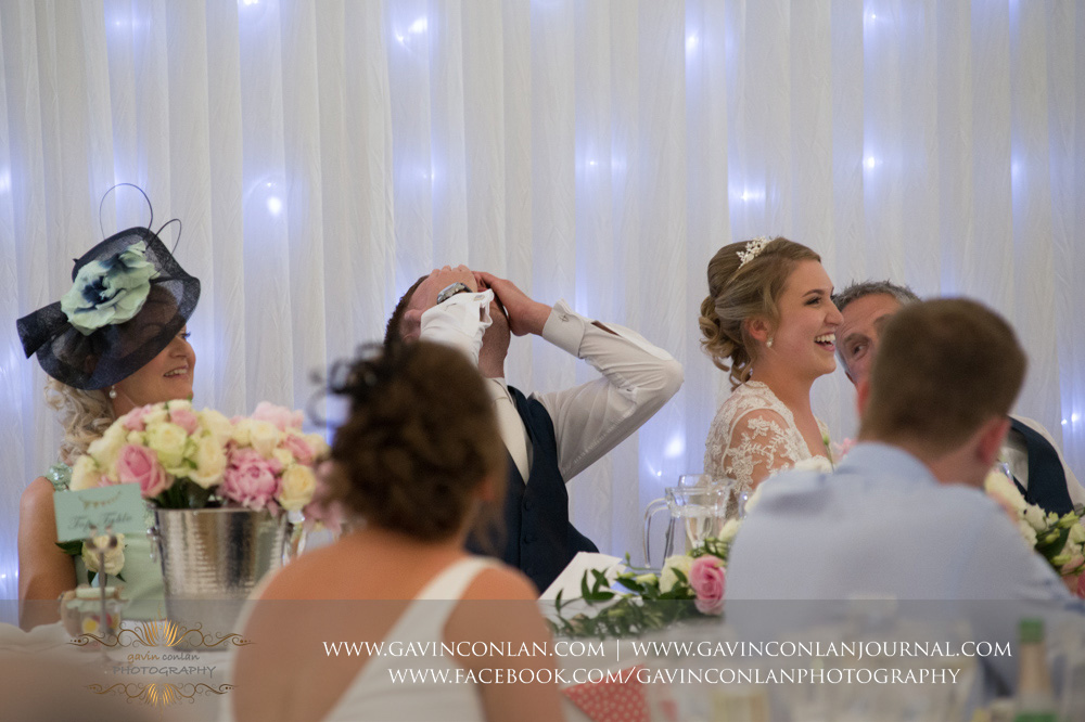 brilliant moment of the groom leaning back with his hands covering face as every one else is laughing during the best men speech. Wedding photography at  Parklands Quendon Hall  by preferred supplier  gavin conlan photography Ltd