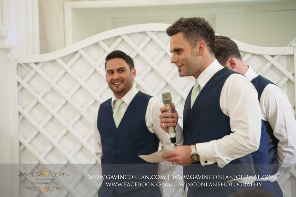 creative portrait of one of the best men during his speech as the other two best men look on with joy. Wedding photography at  Parklands Quendon Hall  by preferred supplier  gavin conlan photography Ltd