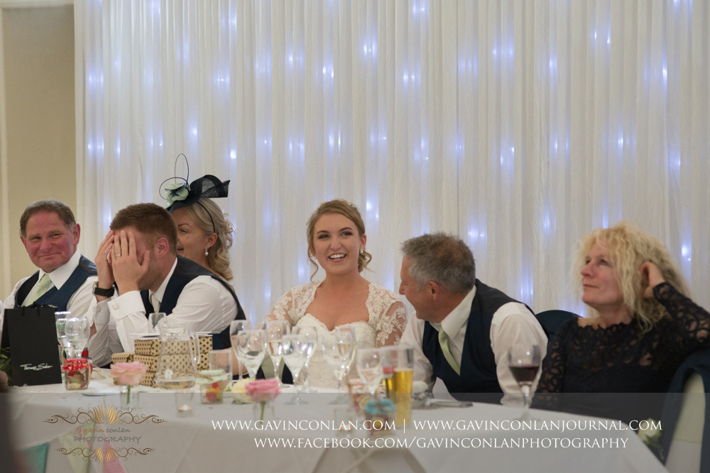 brilliant moment of the groom with his hands covering face as every one else is smiling during the best men speech. Wedding photography at Parklands Quendon Hall by preferred supplier gavin conlan photography Ltd