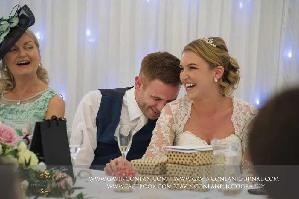 brilliant moment of the groom leaning his face on his brides shoulder as she is laughing during the best men speech. Wedding photography at Parklands Quendon Hall by preferred supplier gavin conlan photography Ltd