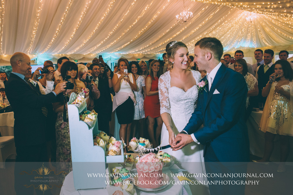 creative portrait of the bride and groom looking at each other smiling as they are about to cut their wedding cupcake with all their guests looking on. Wedding photography at Parklands Quendon Hall by preferred supplier gavin conlan photography Ltd